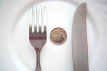 One Ruble Coin On A White Plate Next To Fork And Knife