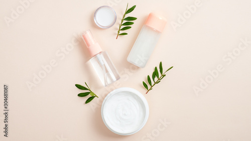 Organic cosmetic bottle containers and jar with white face cream on beige background with green herbal leaves Fototapeta