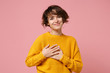 canvas print picture - Smiling pleasant young brunette woman girl in yellow sweater posing isolated on pastel pink background, studio portrait. People lifestyle concept. Mock up copy space. Holding hands crossed on heart.