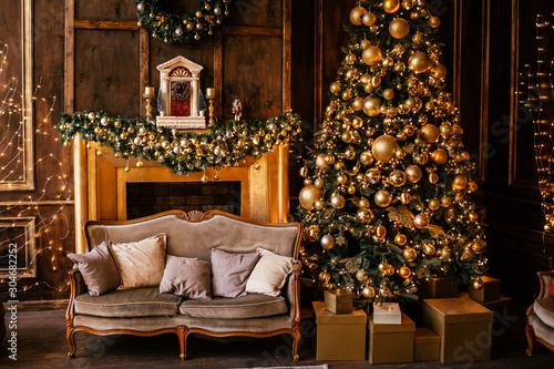 Photo Christmas background with illuminated fir tree with golden decpration and fireplace in living room