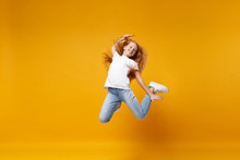 Cheerful Little Ginger Kid Girl 12-13 Years Old In White T-shirt Isolated On Yellow Background Children Portrait. Childhood Lifestyle Concept. Mock Up Copy Space. Having Fun, Fooling Around, Jumping.