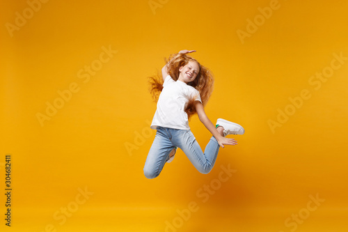 Fotografia Cheerful little ginger kid girl 12-13 years old in white t-shirt isolated on yellow background children portrait