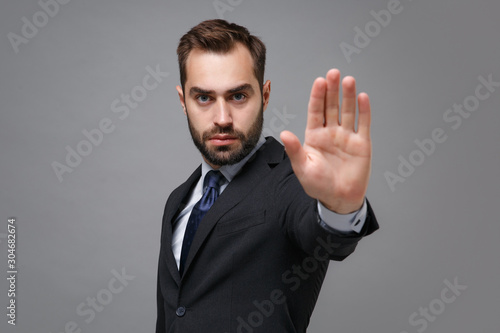 Obraz Serious young bearded business man in classic black suit shirt tie posing isolated on grey background. Achievement career wealth business concept. Mock up copy space. Showing stop gesture with palm. - fototapety do salonu
