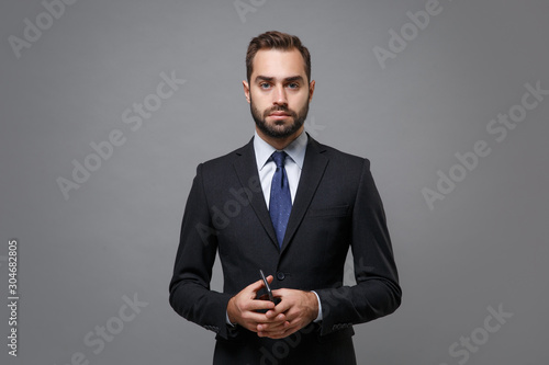 Fotografia Serious young bearded business man in classic suit shirt tie posing isolated on grey background studio portrait