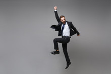 Happy Young Business Man In Classic Black Suit Shirt Tie Posing Isolated On Grey Background. Achievement Career Wealth Business Concept. Mock Up Copy Space. Jumping, Doing Winner Gesture, Screaming.
