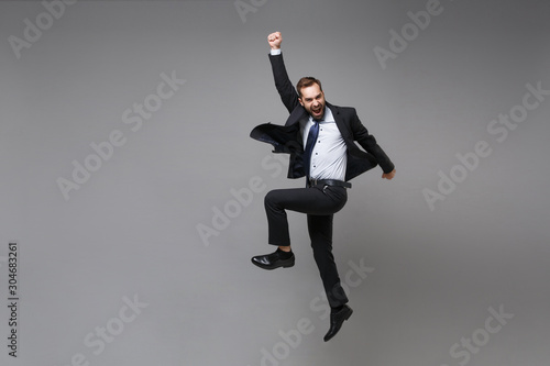 Fotografie, Obraz Happy young business man in classic black suit shirt tie posing isolated on grey background