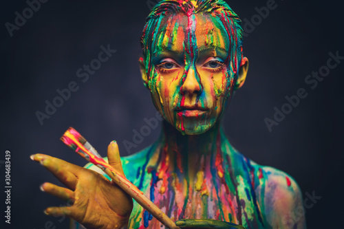 Young woman covered with a colourful paint