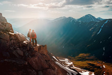 Two Hikers Stands On Cliff In Big Mountains