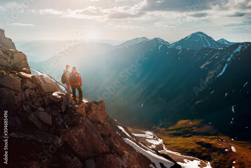 Two hikers stands on cliff in big mountains Wallpaper Mural