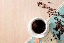 A White Cup Of Coffee With Coffee Beans And Map On Wooden Background