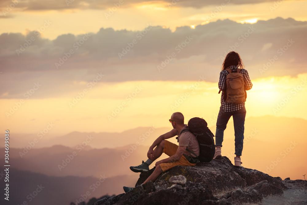 Fototapeta Couple hikers at sunset mountain viewpoint