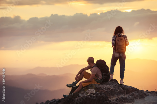 Obraz Couple hikers at sunset mountain viewpoint - fototapety do salonu