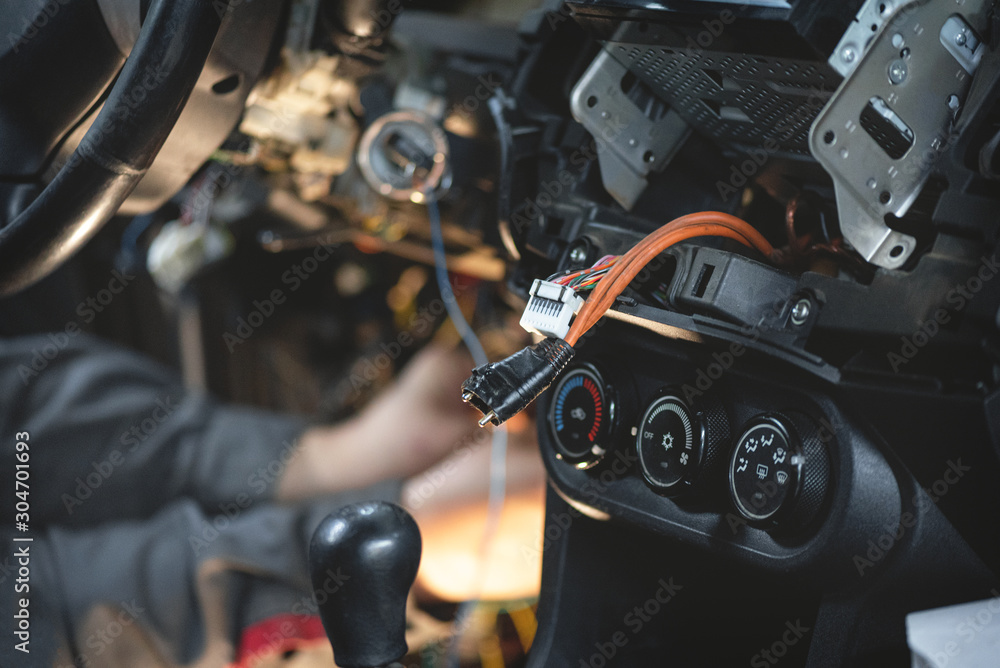 Fototapeta Auto electrician worker is installing a car alarm close up concept.