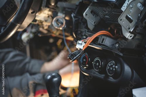 Obraz Auto electrician worker is installing a car alarm close up concept. - fototapety do salonu