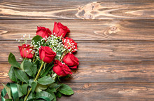 Beautiful Bouquet Of Red Roses And Baby's Breath White Flowers On A Wooden Background, Top View With Copy Space.