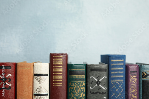 Canvastavla Collection of old books on light blue background. Space for text