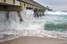 Wooden Fishing Pier With Beach And Waves In Atlantic Ocean In Florida