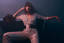 Dark-haired Girl Sitting On A Chair In Violet Light In A Silver Jumpsuit With A Wide Belt, She Has Professional Makeup And Looks In Camera