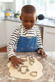 Boy making Christmas cookies at home