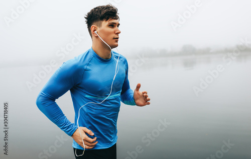 Obraz Horizontal outdoor image of young runner man running in the morning on the fog lake background. Fitness male exercising in the park and listenting the music on earphones. People and sport concept - fototapety do salonu