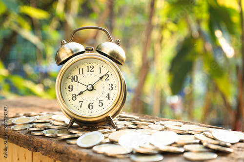 Vintage golden alarm clock with stacks of coin Tablou Canvas