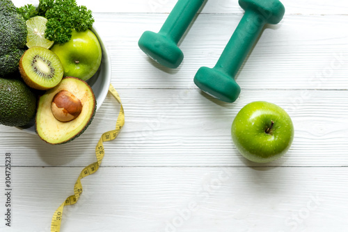 Fototapeta Healthy lifestyle for women diet with dumbbells sport equipment, sneakers, measuring tape, fruit healthy green apples and bottle of water on wooden.  Healthy Concept.. obraz