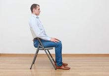 Caucasian Man Sitting On The  Chair In Correct  Posture