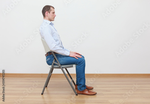 Obraz caucasian man sitting on the  chair in correct  posture - fototapety do salonu