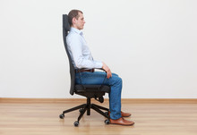 Caucasian Man Sitting On Office Chair In Correct  Position