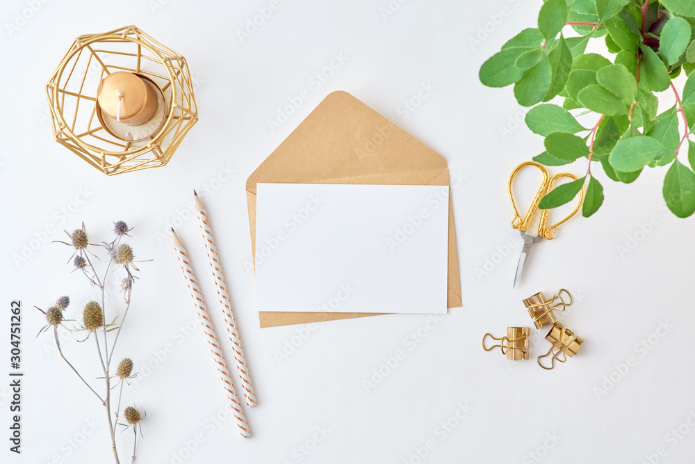 Fototapeta Mockup white greeting card and envelope with branches with green leaves on a light background