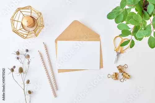 Fotografía  Mockup white greeting card and envelope with branches with green leaves on a lig