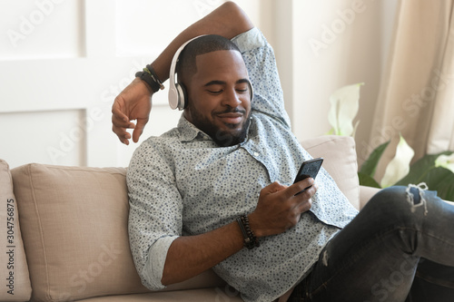Photo Smiling biracial man listen to music in headphones at home