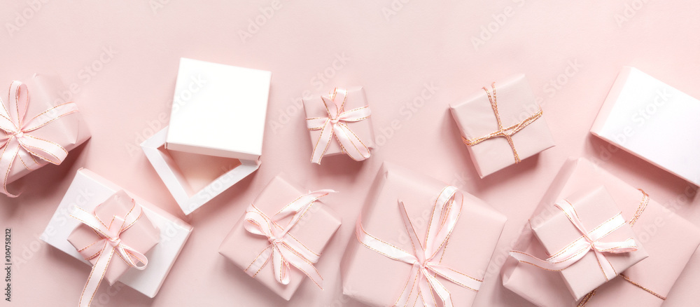 Fototapeta Christmas pink gift  flat lay. Holiday boxes, fir branches on pink background. Christmas winter holiday congratulation invitation birthday wedding.Long banner