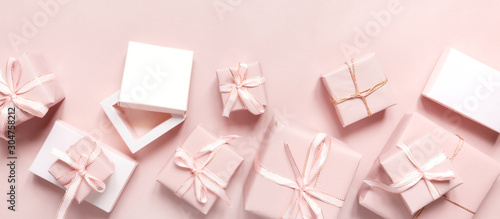Obraz Christmas pink gift  flat lay. Holiday boxes, fir branches on pink background. Christmas winter holiday congratulation invitation birthday wedding.Long banner - fototapety do salonu