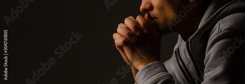 Fotografie, Obraz Religious young man praying to God on dark background, black and white effect
