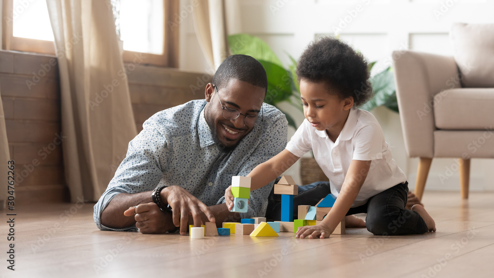 Fototapeta African father and son play with toy blocks on floor