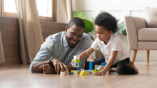 African Father And Son Play With Toy Blocks On Floor
