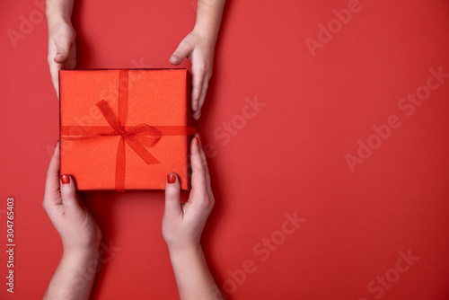 Mother giving christmas gift to son on red background, copy space Canvas Print