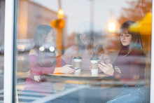 Mother And Daughters Sitting In Cafe Drinking Coffee And Taking. Have Conversation, Happy And Sad. One Sister Chatting On Mobile Phone And Bored Picture Through Window.