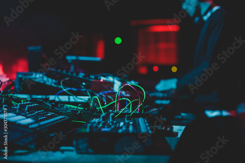 View of Dj mixer and vinyl plate with headphones on a table with DJ playing and mixes the track in the background, during night techno party in the nightclub - 304771079