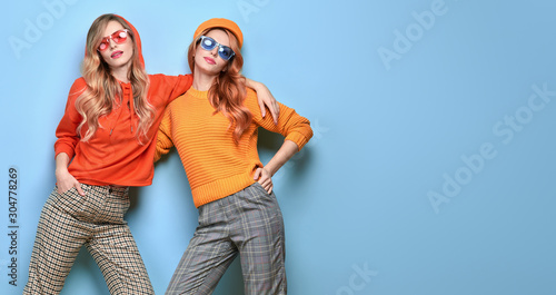 Two Lovable embracing fashionable woman sisters in Trendy orange yellow outfit. Studio shot of Carefree beautiful funny stylish friends smiling on blue. Happy fashion girl, colorful positive banner