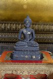Ancient stone statue of Buddha sitting in lotus position.
