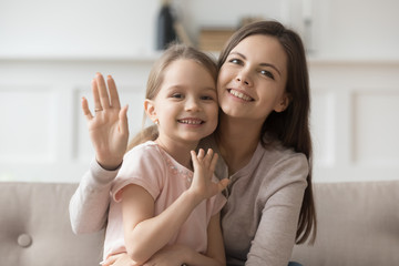 Happy mom and little daughter look at camera waving