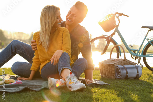 Foto Happy young couple having picnic near lake on sunny day
