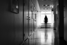 Silhouette Of Person In Motion Blur In Front Of Window In A Hostpital Corridor.