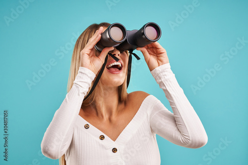 Photo Beautiful adult woman posing over blue background with binoculars