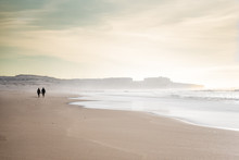People Walking On Windswept Sunny Guincho Beach At Low Tide