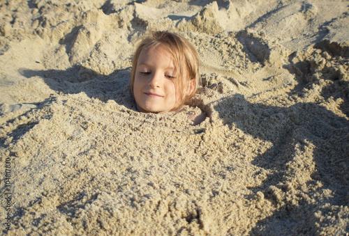 Fototapeta dziewczynka bawiąca się na plaży podczas letnich wakacji nad morzem  obraz