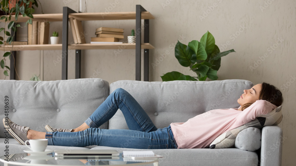 Fototapeta Tired young woman relax at home sleeping on cozy couch