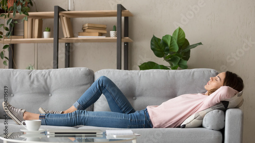 Fotografie, Obraz Tired young woman relax at home sleeping on cozy couch